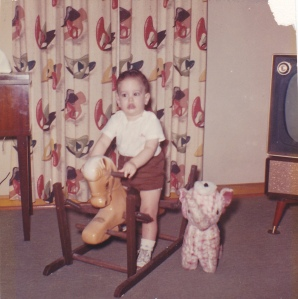My youngest brother Jack Maupin on his rocking horse, stuffed elephant beside him